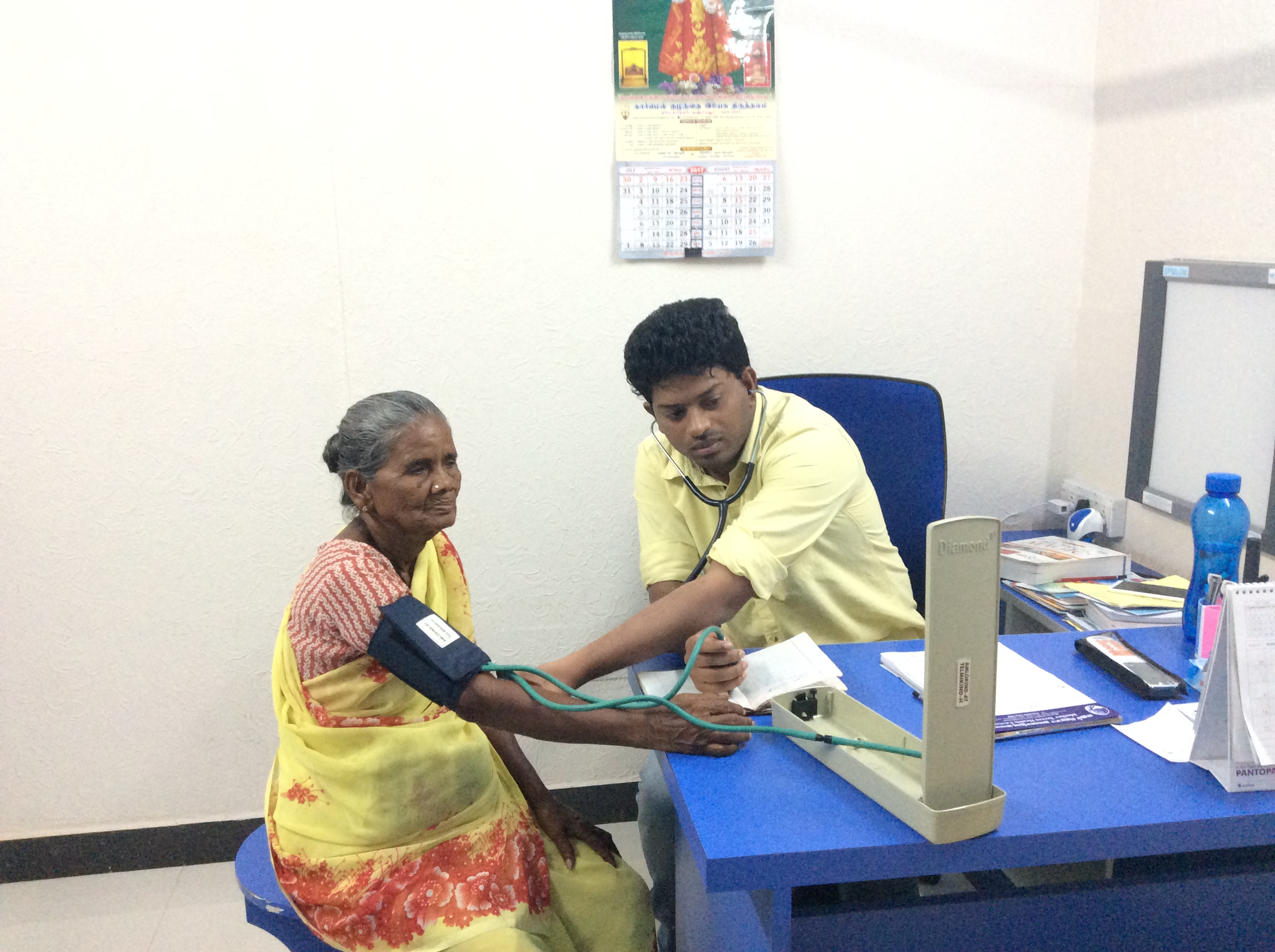 Dr. Sathish examining the patient in the medical camp.