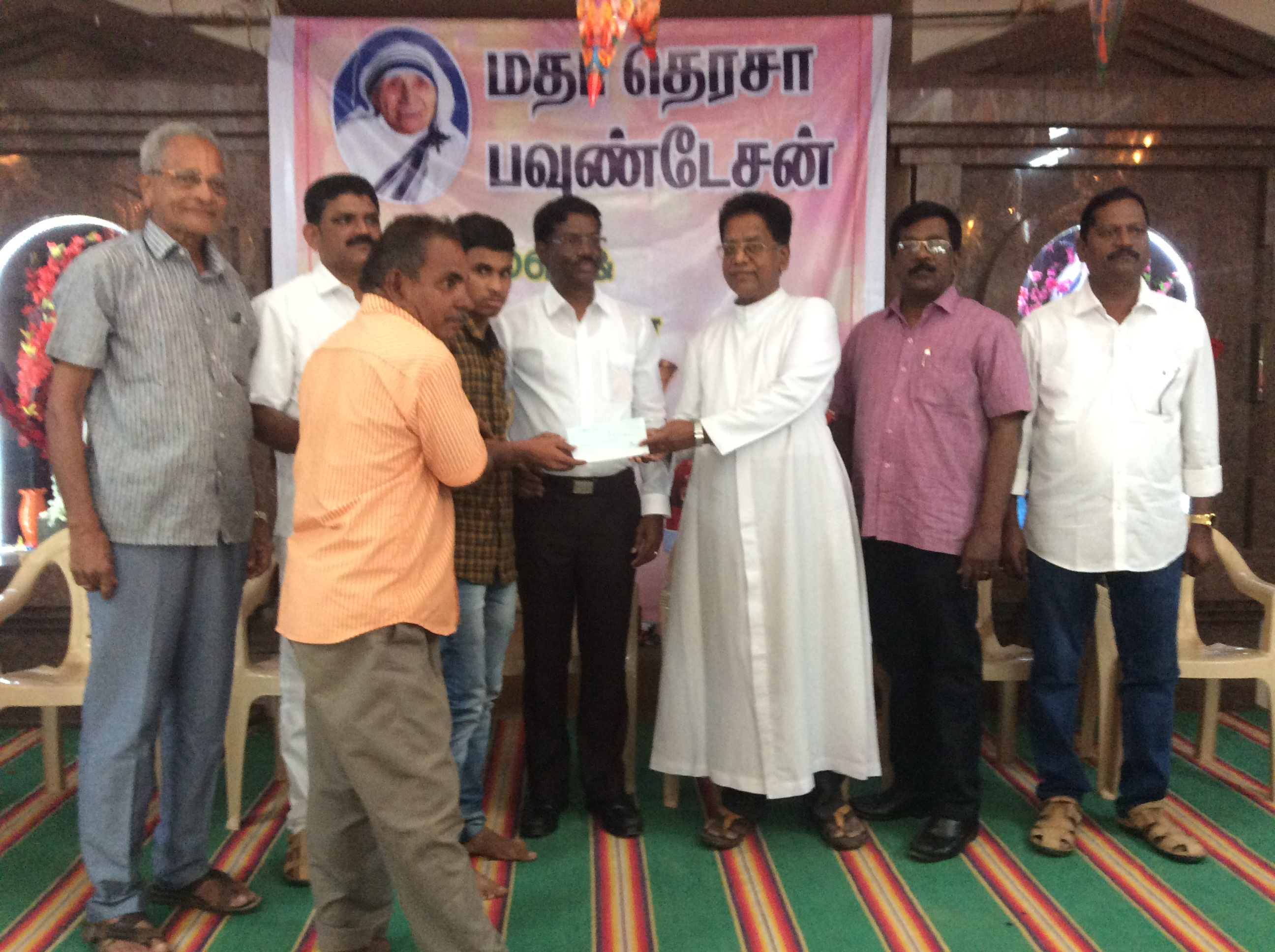 Rev. Fr. Periyanna handing over cheque to Selvan. Muthuraman on behalf of our Foundation